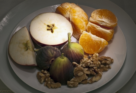 Plate of fruit - apple, figs, nuts and orange
