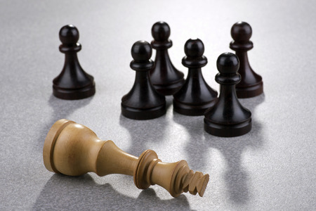 Chess - dead white king with black pawns photo