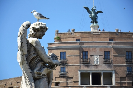 Angel on Ponte Sant Angelo with Castle of the Holy Angel in Rome, Italy  Stock Photo