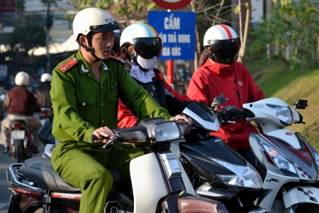 sentenced: Dalat, Vietnam - February 10, 2012: Policeman on motorcycle on February 10, 2012 in Dalat, Vietnam. Musicians Vo Minh Tri and Tran Vu Anh Binh were sentenced to prison on October 30, 2012 on charges of spreading propaganda against the state. Editorial