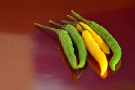 Green and yellow peppers on red background Stock Photo - 16124646