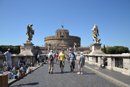Rome, Italy - July 10, 2012: Tourists crossing the Ponte Sant Angelo with Castel Sant Angelo in the background.