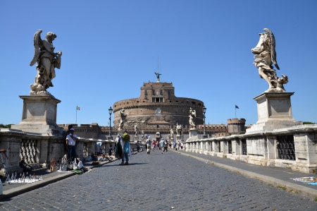 Rome, Italy - July 10, 2012: Tourists crossing the Ponte Sant Angelo with Castel Sant Angelo in the background. Editorial