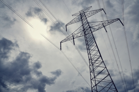 Electricity pylon against sun behind clouds Stock Photo