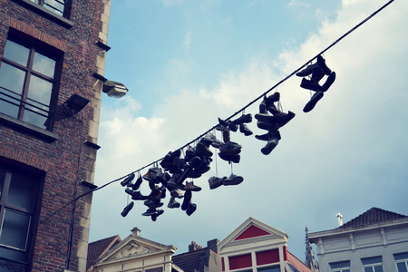 Filtered picutre of shoes hanging from a power line in Ghent, Belgium Standard-Bild