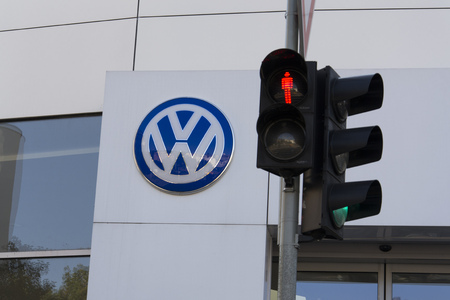 schandaal: PRAGUE, CZECH REPUBLIC - OCTOBER 1: Red colour on traffic light with Volkswagen car maker logo on a building of czech dealership on October 1, 2015 in Prague, Czech republic. Great emission scandal raises around number of Volkswagen Group cars with the EA