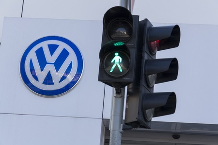 scandal: PRAGUE, CZECH REPUBLIC - OCTOBER 1: Green colour on traffic light with Volkswagen car maker logo on a building of czech dealership on October 1, 2015 in Prague, Czech republic. Great emission scandal raises around number of Volkswagen Group cars with the