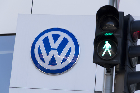 schandaal: PRAGUE, CZECH REPUBLIC - OCTOBER 1: Green colour on traffic light with Volkswagen car maker logo on a building of czech dealership on October 1, 2015 in Prague, Czech republic. Great emission scandal raises around number of Volkswagen Group cars with the