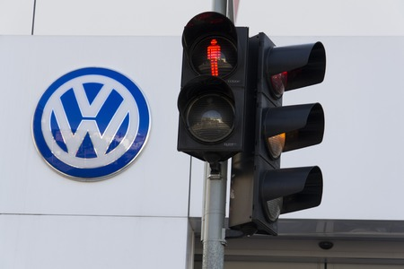 scandal: PRAGUE, CZECH REPUBLIC - OCTOBER 1: Red colour on traffic light with Volkswagen car maker logo on a building of czech dealership on October 1, 2015 in Prague, Czech republic. Great emission scandal raises around number of Volkswagen Group cars with the EA