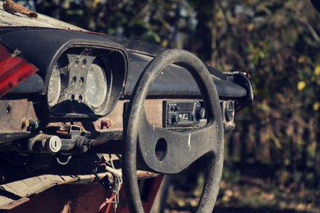 weather gauge: Filtered vintage photo of steering wheel and rusty speedometer on car control panel