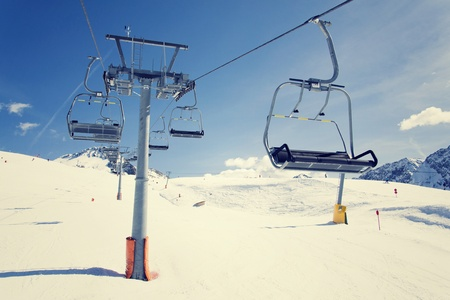 mountains and sky: Filtered vintage photo of ski chair lift on sunny winter day