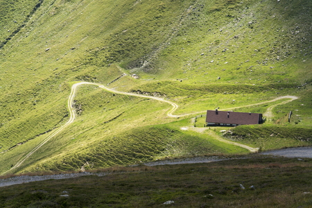 meander: Empty mountain road meander to lonesome house in Alps, Austria Stock Photo