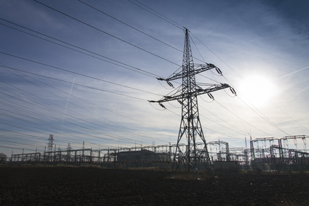 Electricity pylon from distribution power station with sun in background