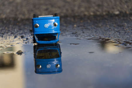 scrap trade: PRAGUE, CZECH REPUBLIC - MARCH 23: Vintage tinwork toy car with Volkswagen logo in a puddle in front of the dealership on March 23, 2016 in Prague, Czech Republic.