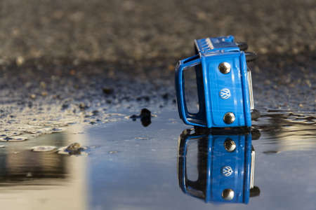 scrap trade: PRAGUE, CZECH REPUBLIC- MARCH 23: Vintage tinwork toy car with Volkswagen logo in a puddle in front of the dealership on March 23, 2016 in Prague, Czech Republic. Editorial