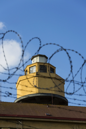 trespass: Guarding tower behind barbed wire fence stretched around prison walls
