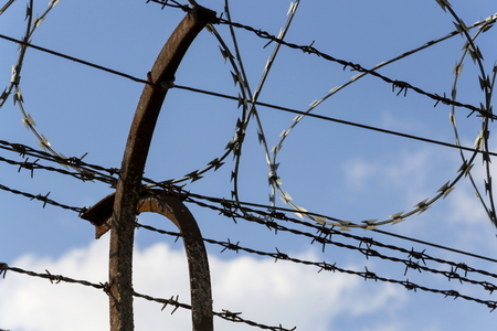 prison wall: Prison wall barbed wire fence detail with blue sky in background Stock Photo