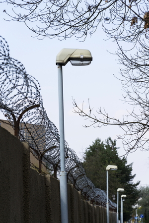 Street lamp beside barbed wire fence around prison walls