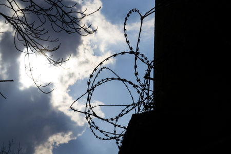prison wall: Dramatic clouds behind barbed wire fence on a prison wall