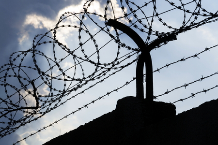 wall clouds: Dramatic clouds behind barbed wire fence on a prison wall