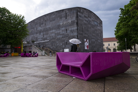 6 people: VIENNA, AUSTRIA - MAY 6: People rest on red benches in front of the MUMOK, Museum of modern art  at the MuseumsQuartier on 6 May 2012 in Vienna, Austria.