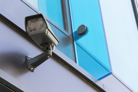 big brother spy: Grey security camera attached to wall blue windows in background Stock Photo