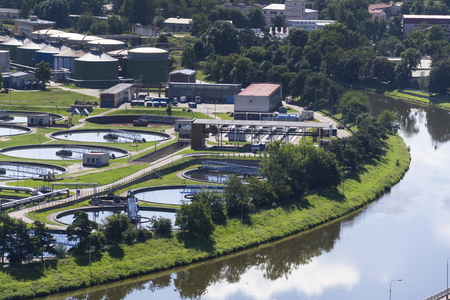water treatment plant: Aerial view of river meandering around sewage water treatment plant