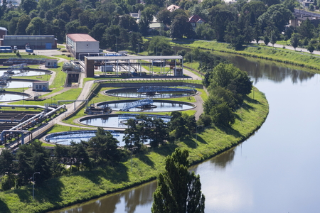aguas residuales: Aerial view of river meandering around sewage water treatment plant