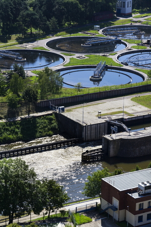 aguas residuales: Sewage water treatment plant with river in foreground aerial view Foto de archivo