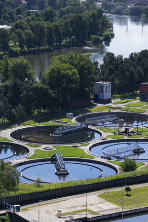 aguas residuales: Sewage water treatment plant with river in background aerial view
