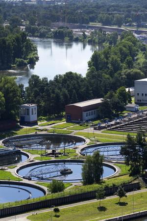 aguas residuales: planta de tratamiento de aguas residuales con el río en el fondo vista aérea
