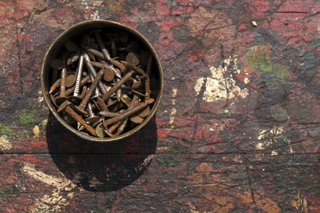 rusty nail: Nails in rusty tin can on a wooden background