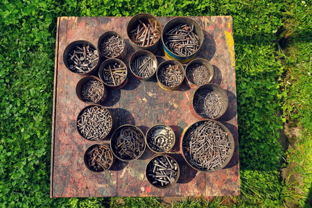 rusty nail: Nails and screws in rusty cans on wood grass background