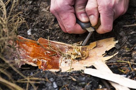 Mannelijke hand begint vuur met magnesium brand staal, brand spits
