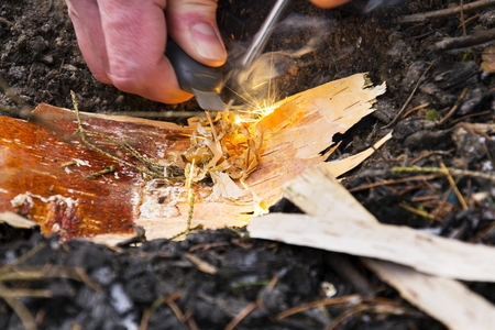 Male hand starts fire with magnesium fire steel, fire striker