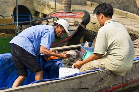 MY THO, VIETNAM - FEBRUARY 14: Fisherman sells fish on boat on February 14, 2012 in My Tho, Vietnam.