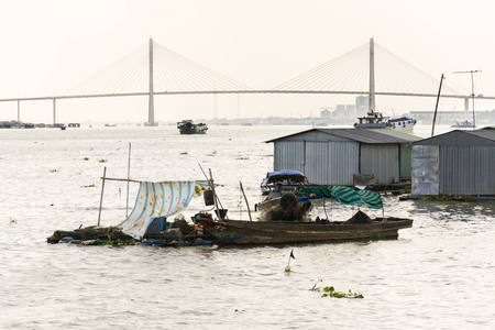 MY THO, VIETNAM - FEBRUARY 13: Man sails on ratty boat with fish farm raft houses floating on Mekong river with Rach Mieu Bridge in background on February 13, 2012 in My Tho, Vietnam.