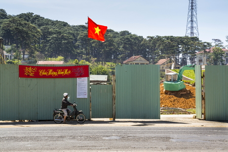 DALAT, VIETNAM - FEBRUARY 10: Man on motorbike in front of construction site with excavator and Vietnamese flag on February 10, 2012 in Dalat, Vietnam. Editorial