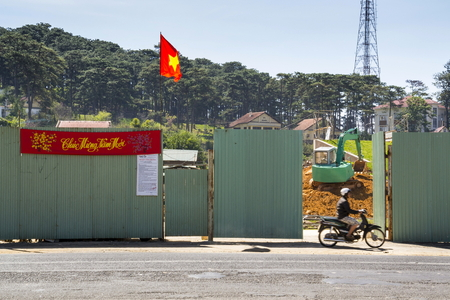 cooter: DALAT, VIETNAM - FEBRUARY 10: Man on motorbike in front of construction site with excavator and Vietnamese flag on February 10, 2012 in Dalat, Vietnam. Editorial