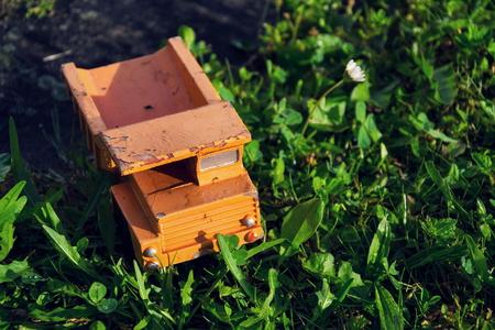 Filtered vintage orange car toy truck on green grass