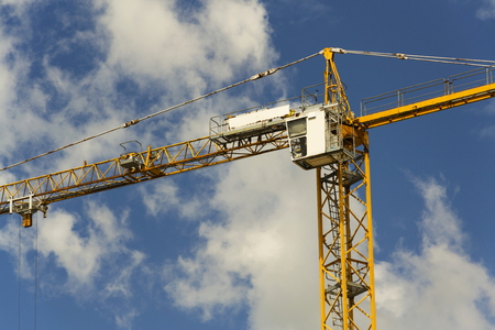 Yellow crane on construction site with blue sky background