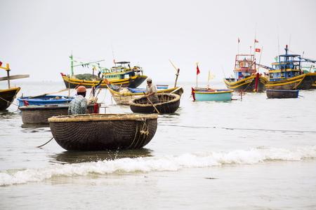 MUI NE, VIETNAM - FEBRUARY 7: Fishermen with colorful fishing boats on February 7, 2012 in Mui Ne, Vietnam.