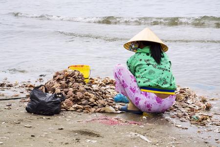 MUI NE, VIETNAM - FEBRUARY 7: Women processing seashells with fishing boats in background on February 7, 2012 in Mui Ne, Vietnam.
