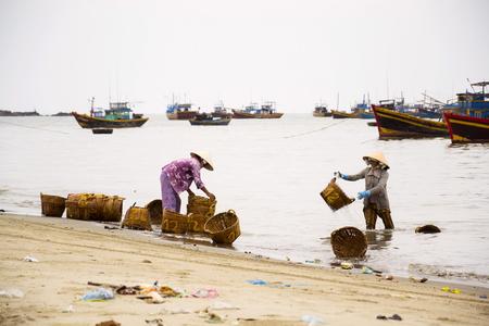 MUI NE, VIETNAM - FEBRUARY 7: Woman washing baskets for anchovies used for fish sauce on February 7, 2012 in Mui Ne, Vietnam.