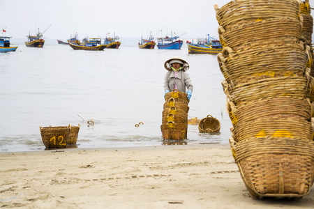 ne: MUI NE, VIETNAM - FEBRUARY 7: Woman washing baskets for anchovies used for fish sauce on February 7, 2012 in Mui Ne, Vietnam.