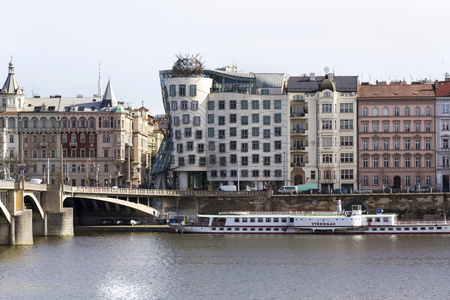 PRAGUE, CZECH REPUBLIC - MARCH 3: Boat floating in front of the Dancing House, nicknamed Fred and Ginger, completed in 1996 for Nationale-Nederlanden by Vlado Milunic and Frank Gehry on March 3, 2017 in Prague, Czech republic. Editorial