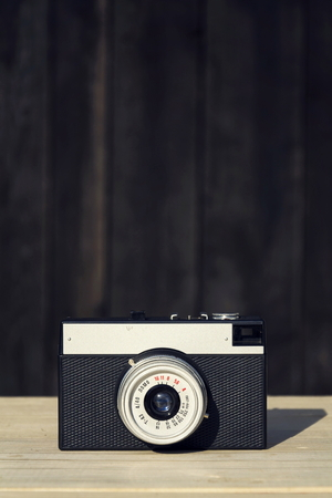 Old vintage filtered camera on wooden background Stock Photo