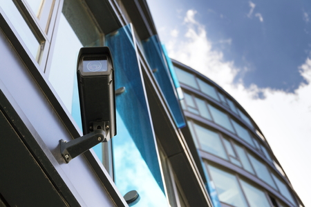 Grey security camera with window reflecting blue sky clouds Stock Photo