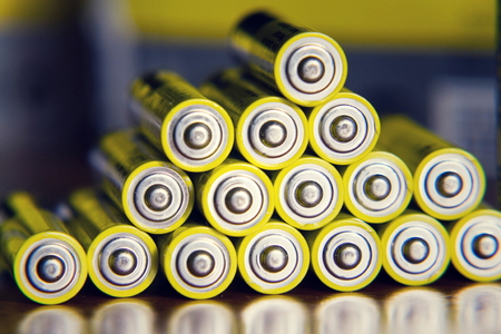 Stack of yellow AA batteries close up abstract color background Foto de archivo