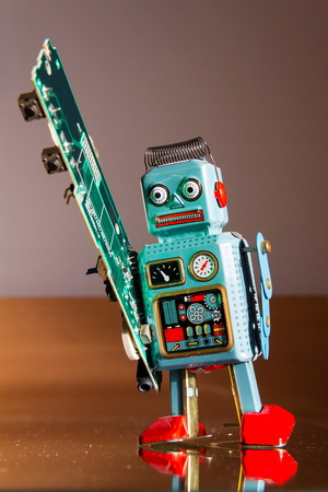 Tin toy robot carries computer circuit board, artificial intelligence concept Stock Photo